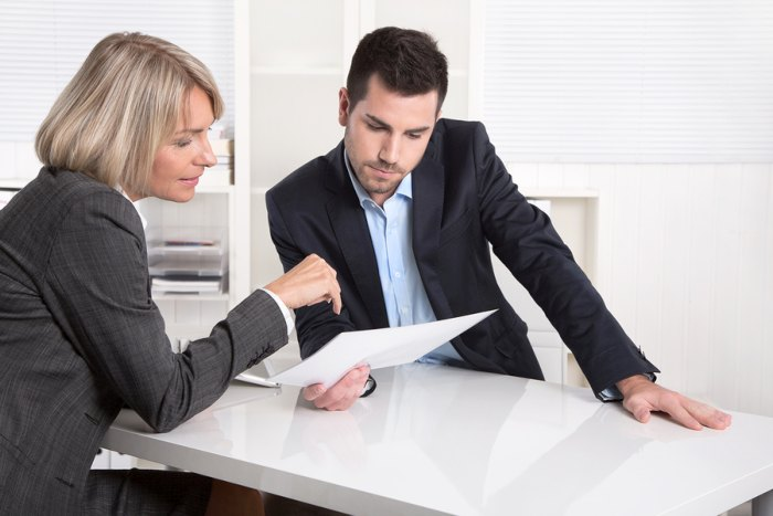 Man and woman at desk discussing paperwork and finance